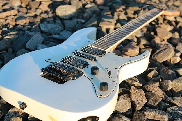 Weiße e-gitarre auf den bahngleisen und industriegrauer stein