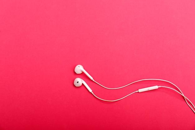 Weiße earphons auf rosa hintergrund. kopieren sie platz für text.