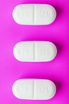Weiße ecstasy-pillen in einer reihe auf einem rosa oberflächenisolat