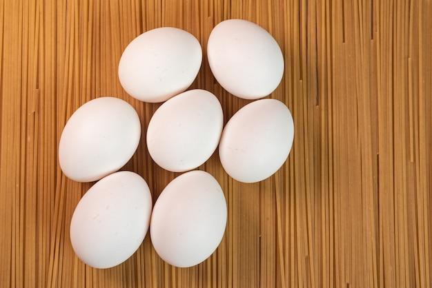 Weiße eier auf den rohen nudeln