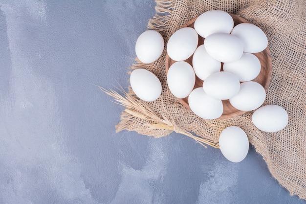 Weiße eier auf sackleinen.