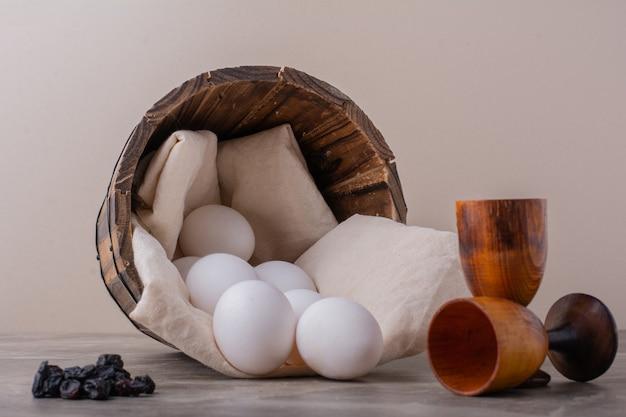 Weiße eier aus einem holzeimer.