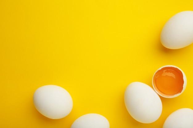 Weiße eier der osterdekoration auf gelbem hintergrund.