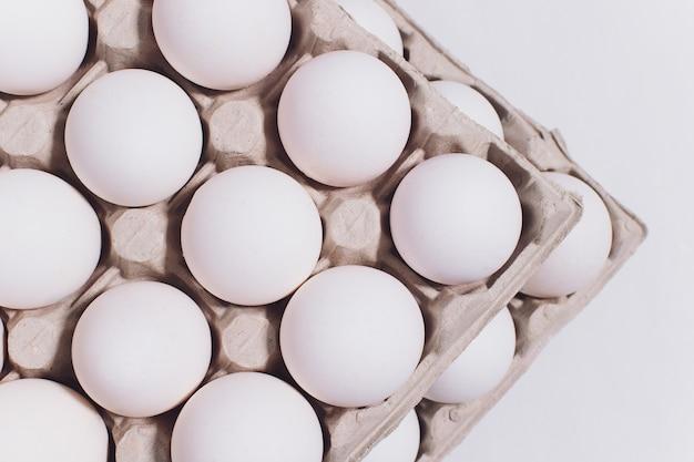 Weiße eier einer henne in der harmlosen, pappverpackung auf weiß