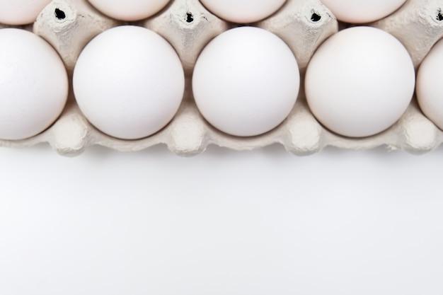 Weiße eier im recycelten karton gepressten kastenbehälter auf weißem tisch mit kopienraum.