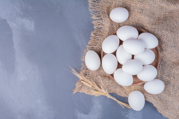 Weiße eier in einer holzplatte auf der sackleinen