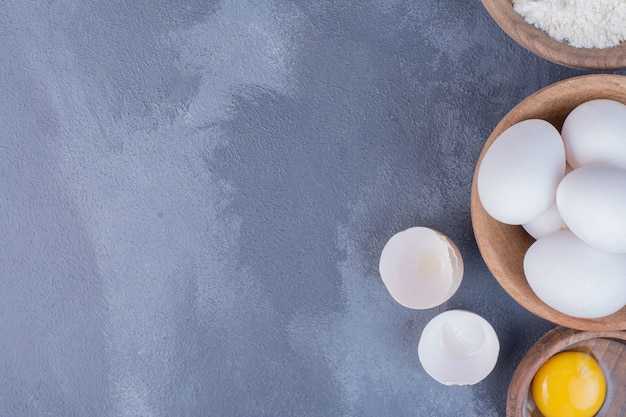 Weiße eier in einer holzschale mit einem gelben eigelb herum.