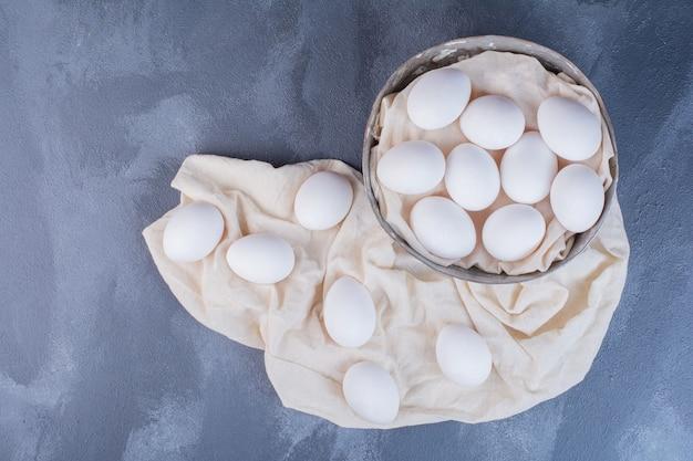 Weiße eier in einer metallischen tasse und auf dem handtuch