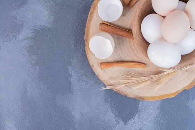 Weiße eier in einer tasse auf holzplatte.