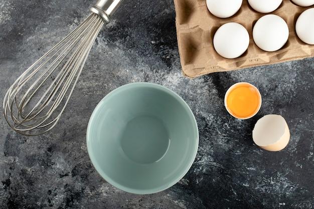Weiße eier in kartonbehälter, schüssel und schnurrhaar auf marmoroberfläche.