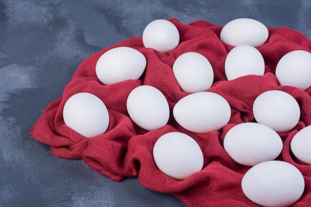 Weiße eier isoliert auf einem stück roter tischdecke