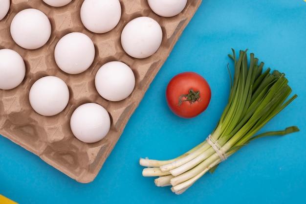 Weiße eier mit tomaten und zwiebeln