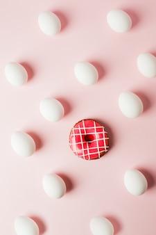 Weiße eier und rosa donut auf einem hellrosa hintergrund mit reflexion der schatten