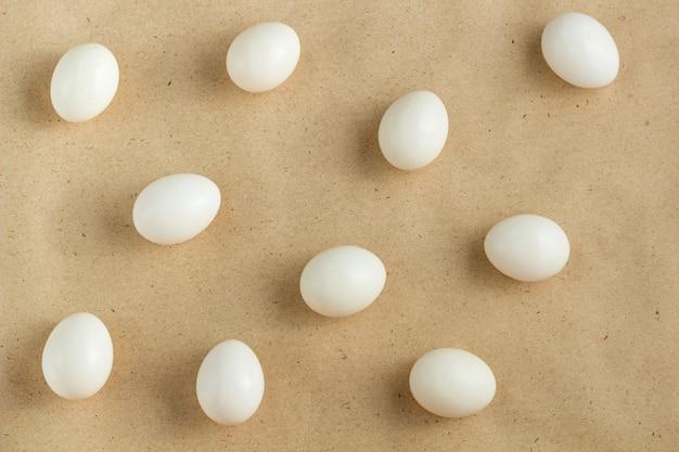 Weiße eier zerstreut auf braunen rustikalen hintergrund