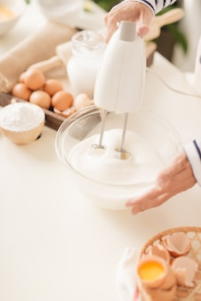 Weiße eiercreme in einer schüssel mit einem motormischer mischen