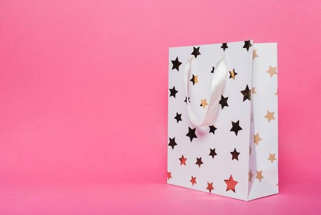 Weiße einkaufstasche mit sternformmuster auf rosa hintergrund