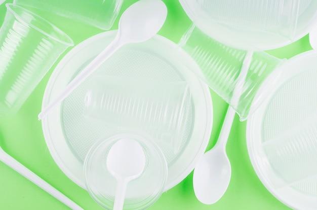 Weiße einwegbecher, teller, gabeln, messer auf hellgrünem hintergrund, nahaufnahme - umweltproblemkonzept, kopierraum