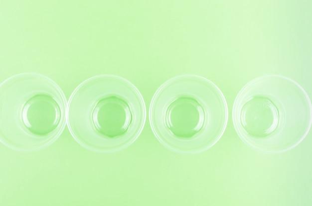 Weiße einwegbecher, teller, gabeln, messer auf hellgrünem hintergrund, nahaufnahme - umweltproblemkonzept