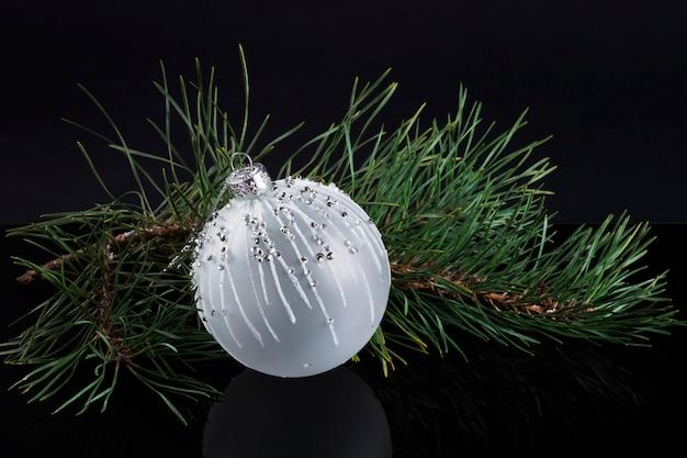 Weiße elegante kugel auf weihnachtsbaumzweig auf schwarzem hintergrund