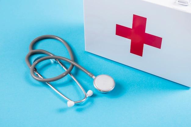 Weiße erste-hilfe-ausrüstung und stethoskop auf blauem hintergrund