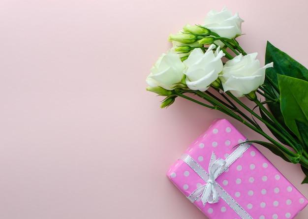 Weiße eustomablumen und rosa geschenkbox