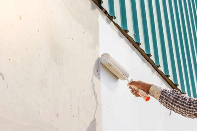 Weiße farbanstrichwand mit rolle in der hand
