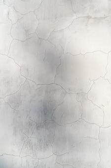 Weiße farbe der leeren rissigen betonwand für texturhintergrund
