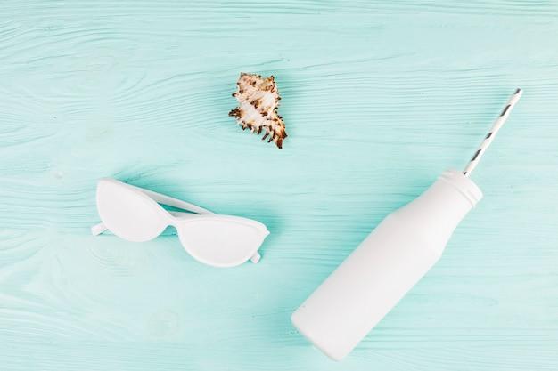 Weiße farbige sonnenbrille nahe flasche mit stroh