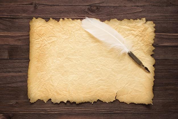 Weiße feder und altes papier auf holzoberfläche
