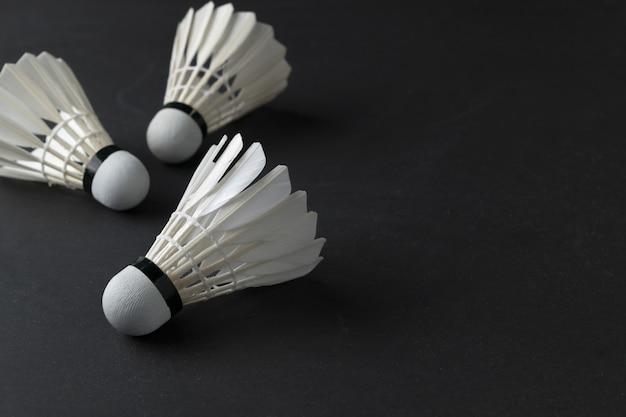 Weiße federbälle auf schwarzem hintergrund. sportkonzept, konzeptsieger, kopieren raumbild für ihren text
