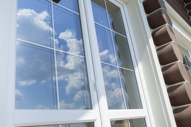 Weiße fenstersprossen aus kunststoff mit der reflexion des blauen bewölkten himmels