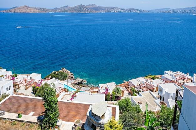 Weiße ferienvillenhäuser im resort mit meerblick und swimmingpool sowie palmen