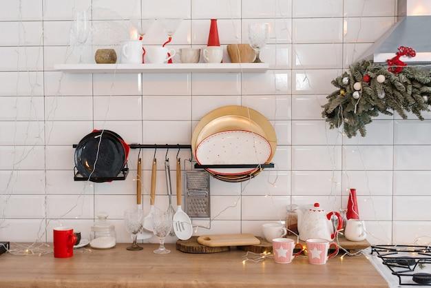 Weiße festliche küchenfliesen an der wand weißer kühlschrank rote dekorelemente weihnachten