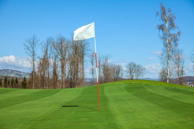 Weiße flagge in der mitte eines golfplatzes in otocec, slowenien