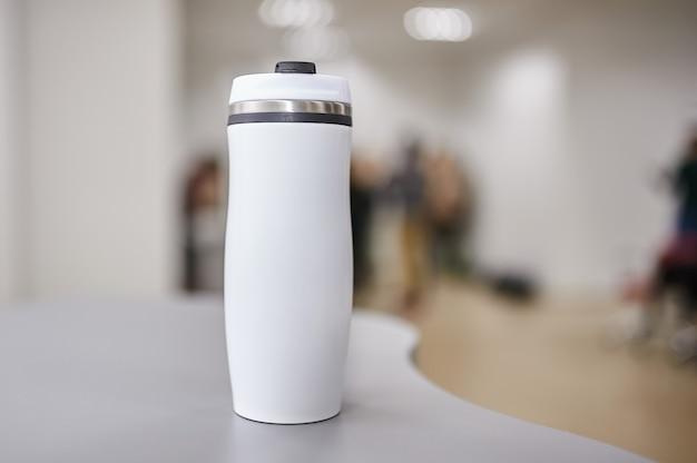 Weiße flasche für wasser verwischte leute auf hintergrund.