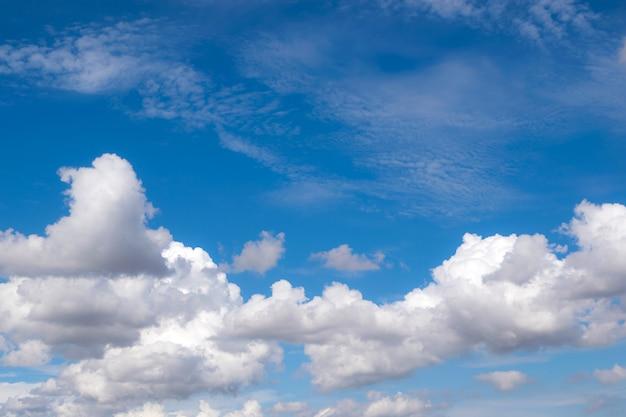 Weiße flaumige wolken im blauen himmel für hintergrund- oder backgropnaturkonzept