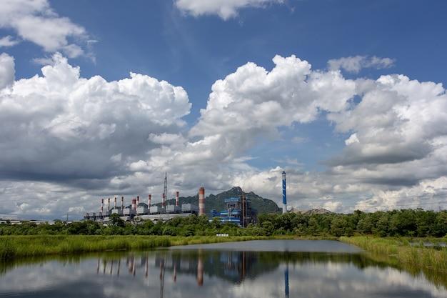 Weiße flaumige wolken im hintergrund des blauen himmels und des kraftwerkes