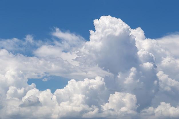 Weiße flaumige wolken im hintergrund des blauen himmels
