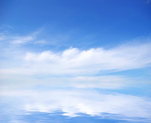 Weiße flaumige wolken mit regenbogen im blauen himmel