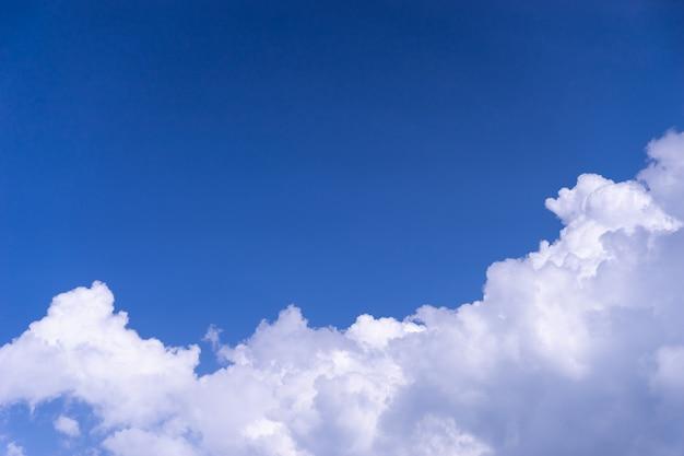 Weiße flauschige wolke auf hellem blauem himmel mit kopienraum am himmel
