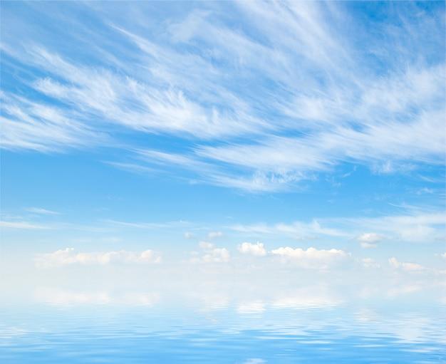 Weiße flauschige wolken mit regenbogen im blauen himmel