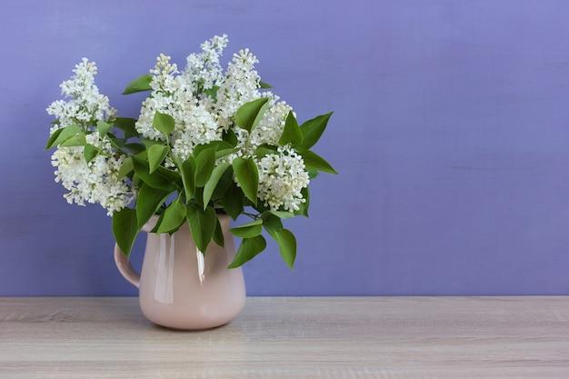 Weiße flieder auf lila hintergrund. gartenfrühlingsblumen in einem krug.