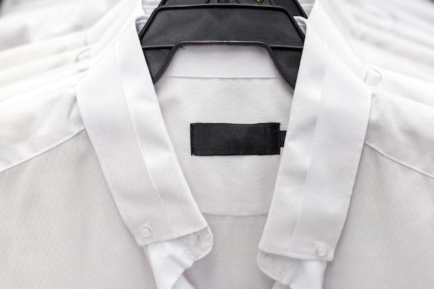 Weiße formale hemden, die an einem aufhänger hängen