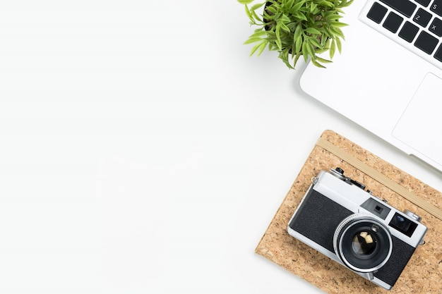 Weiße fotografentischtabelle mit filmkamera, laptop und versorgungen. draufsicht mit kopienraum, flach legen.