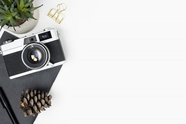 Weiße fotografschreibtischtabelle mit filmkamera und büroartikel. draufsicht mit kopienraum, flache lage.