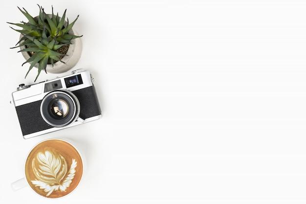 Weiße fotografschreibtischtabelle mit filmkamera und schale lattekaffee. draufsicht mit kopienraum, flache lage.