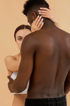 Weiße frau der nahaufnahme, die schwarzen mann hält