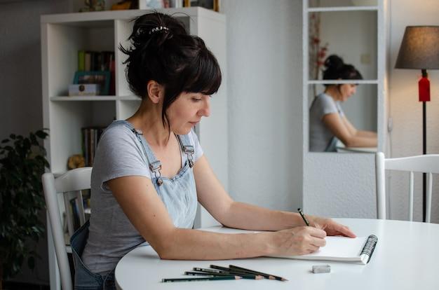 Weiße frau, die zu hause in einem skizzenblock zeichnet