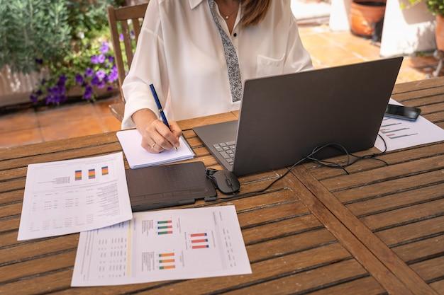 Weiße frau telearbeit im garten mit laptop und notebook.
