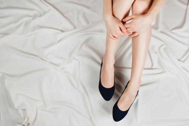 Weiße frauenbeine in hochhackigen dunkelblauen schuhen, die mit weißen laken auf dem bett sitzen.